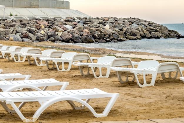 Lit blanc sur la plage de sable à la mer, concept de repos en mer d'été.