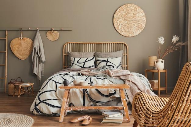 Lit en bois dans un intérieur de chambre neutre élégant avec mobilier design, décoration, tapis, banc, fleurs séchées dans un vase, accessoires personnels élégants dans la décoration intérieure