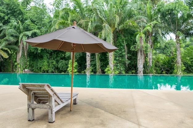 Lit de bronzage en bois avec parasol à côté de la piscine moderne