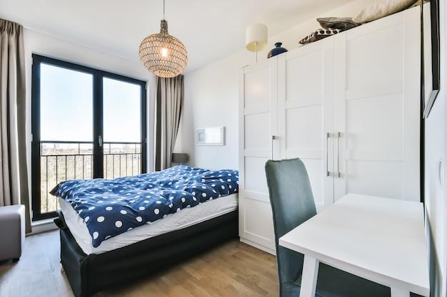 Lit confortable avec couette tachetée situé près d'une armoire et d'une table avec chaise dans une chambre de style minimaliste dans un appartement moderne