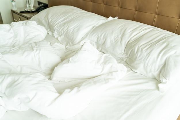 Lit en désordre avec oreiller blanc et couverture sur lit