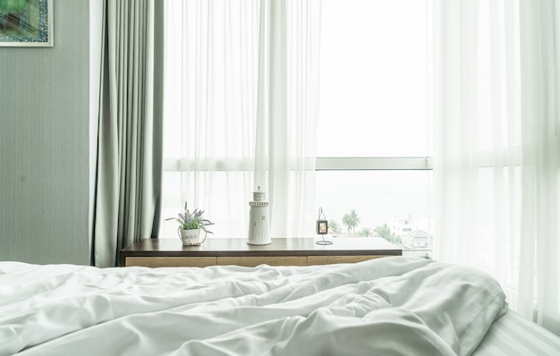 Lit en désordre avec rideau et fenêtre