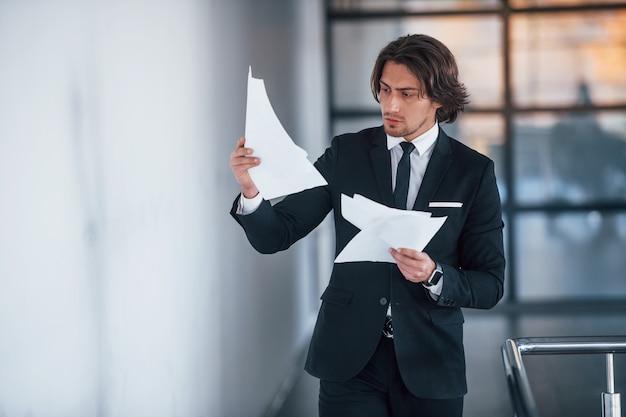 Lit des documents. portrait de beau jeune homme d'affaires en costume noir et cravate.