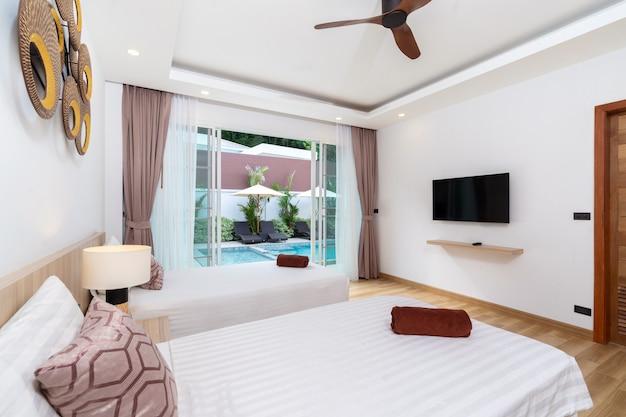 Lit double dans une chambre spacieuse avec ventilateur de plafond et accès à la piscine
