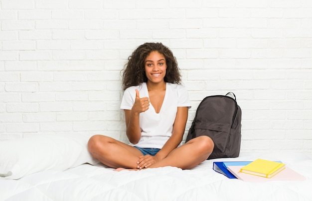 Lit de femme jeune étudiant afro-américain souriant et levant le pouce vers le haut