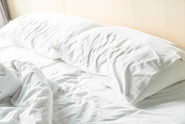 Lit froissé avec oreiller en désordre blanc