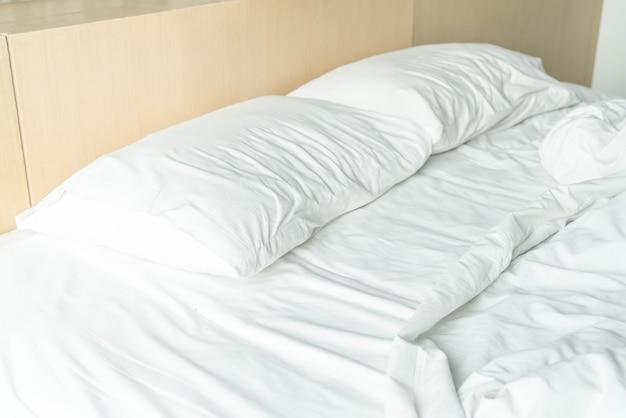 Lit froissé avec oreiller malpropre blanc