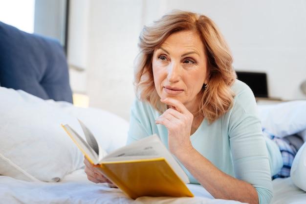 Lit inachevé. femme mûre curieuse réfléchie portant des vêtements domestiques confortables tout en se relaxant au lit et en lisant