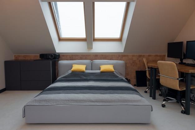 Lit king-size avec literie jaune et grise dans une chambre moderne. intérieur de la chambre élégant avec lit confortable et lieu de travail.