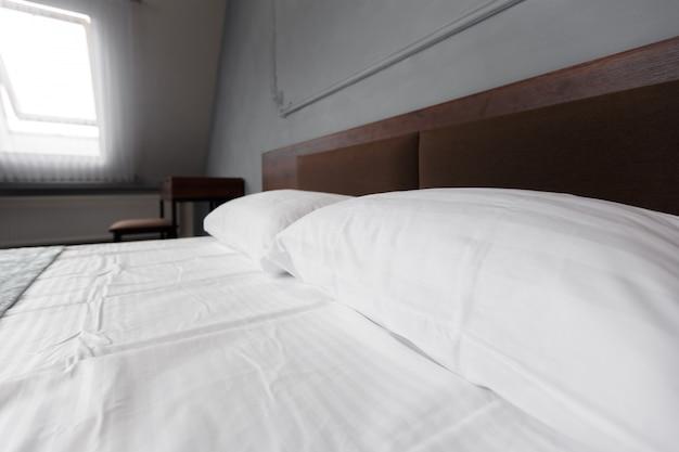 Lit maid-up avec des oreillers et des draps blancs propres dans la salle de beauté.