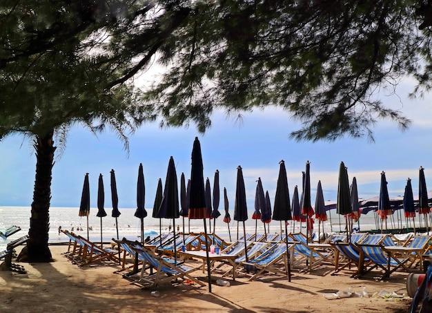 Lit de plage, parasol et des déchets en plastique sur la plage tropicale