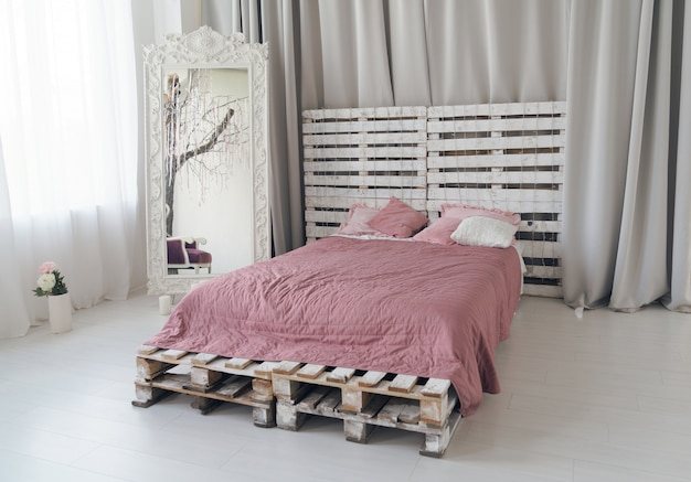 Lit queen-size fait de palettes en bois et grand miroir en bois dans une chambre lumineuse
