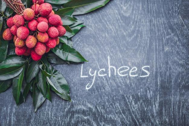 Litchi bio frais et feuilles de litchi sur une surface en bois rustique