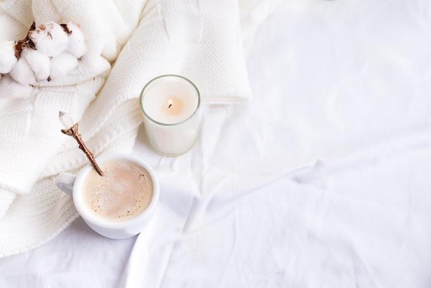 Literie avec un plaid moelleux et une tasse de café, des fleurs en coton et une bougie.
