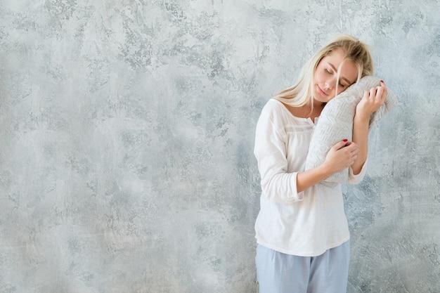 Literie de qualité et confort de couchage. femme debout les yeux fermés tenant une couverture en tricot doux.