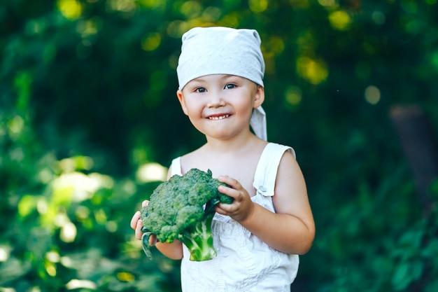 Litle garçon d'agriculteur souriant heureux en salopette blanche et bandeau gris tenant des brocolis frais dans les mains.
