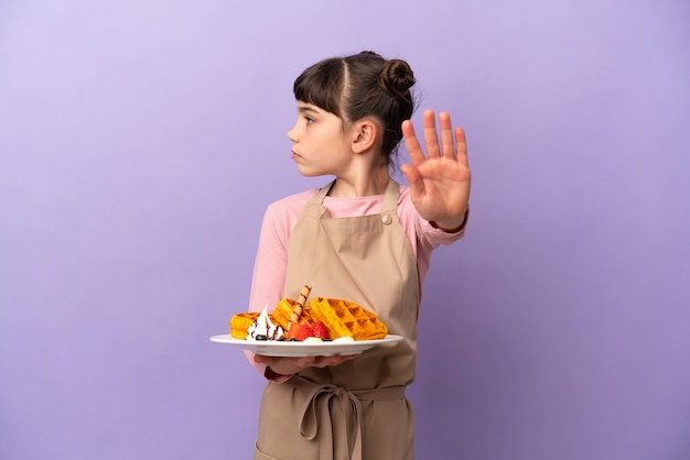 Little caucasian girl holding gaufres isolé sur mur violet faisant le geste d'arrêt et déçu