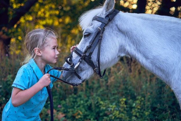 Little kid girl holding câlins son cheval poney isolé à l'extérieur