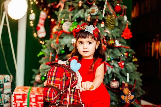Littlle fille en robe rouge se trouve devant un arbre de noël vert dans la chambre