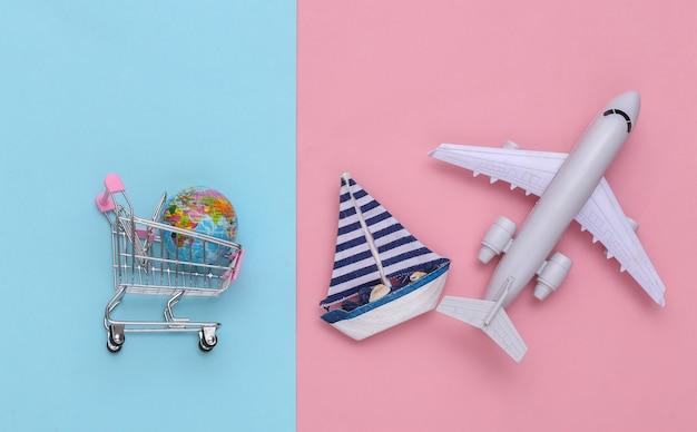 Livraison, achats mondiaux. panier avec globe, voilier et avion sur fond pastel rose bleu. vue de dessus