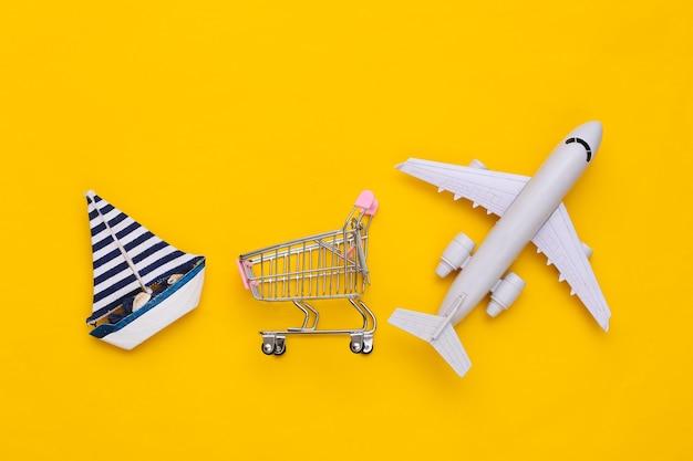 Livraison, achats mondiaux. panier avec voilier et avion sur fond jaune. vue de dessus