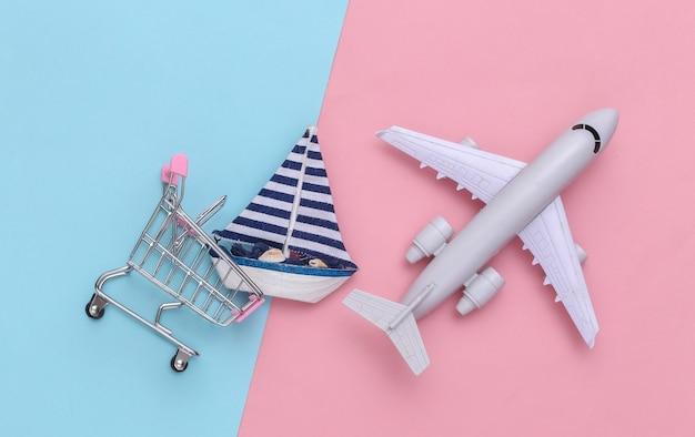 Livraison, achats mondiaux. panier avec voilier et avion sur fond pastel rose bleu. vue de dessus