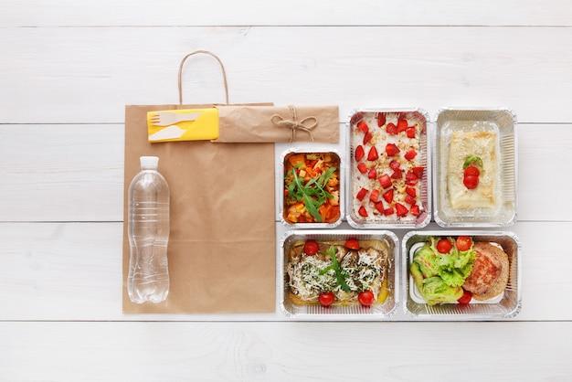 Livraison d'aliments sains, repas quotidiens et collations. nutrition, légumes, flocons d'avoine, viande et bouteille d'eau dans des boîtes en aluminium et emballage en papier brun. vue de dessus, mise à plat au bois blanc avec espace de copie