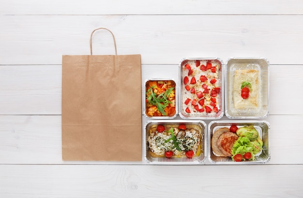 Livraison d'aliments sains, repas quotidiens et collations. nutrition, légumes, viande et fruits dans des boîtes en aluminium et emballage de sac en papier brun. vue de dessus, mise à plat au bois blanc avec espace de copie
