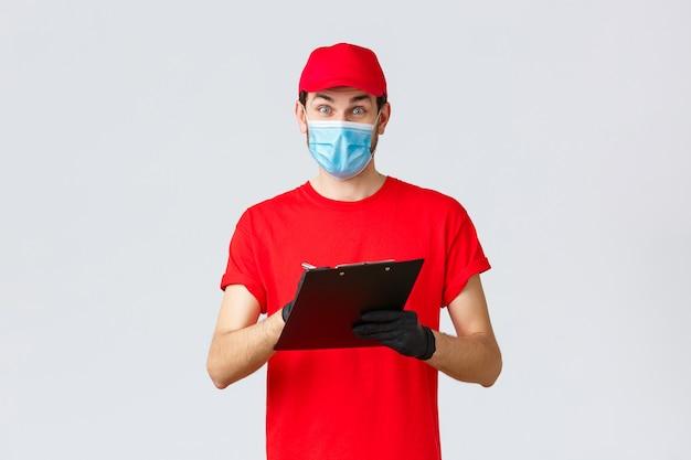 Livraison de colis et colis, livraison quarantaine covid-19, ordres de virement. courrier enthousiaste en uniforme rouge avec masque facial et gants, notant l'adresse de commande, tenant le presse-papiers
