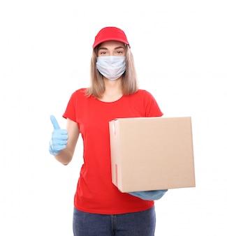Livraison à domicile, commande en ligne. courrier féminin dans un masque médical et des gants en caoutchouc avec une boîte, avec un colis dans ses mains. livraison de nourriture pendant la pandémie de coronavirus en quarantaine