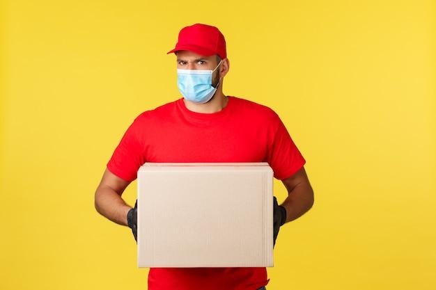 Livraison express pendant la pandémie, covid-19, expédition sûre, concept d'achat en ligne. un coursier indécis ou suspect ressent de l'incrédulité, hésite à donner la boîte de commande à la mauvaise personne, tient la boîte d'emballage