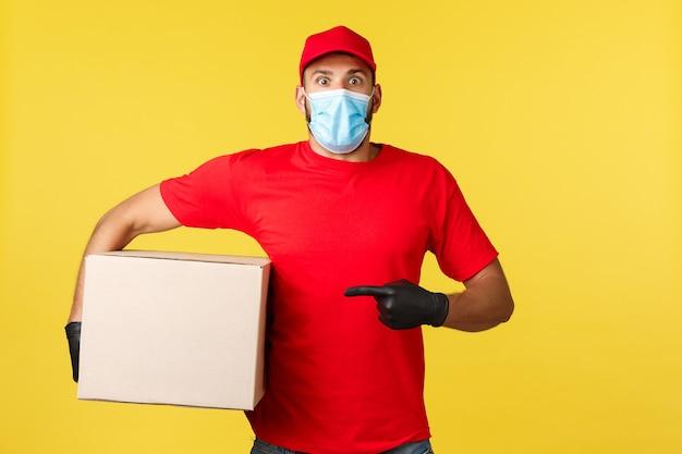Livraison express pendant la pandémie, covid-19, expédition sûre, concept de magasinage. courrier haletant choqué regardant la caméra sans voix en pointant vers la boîte, transportant le paquet, mauvaise adresse, fond jaune