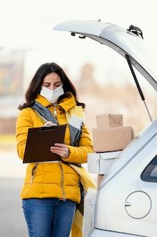 Livraison femme avec masque transportant un paquet