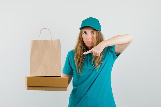 Livraison femme pointant sur sac en papier sur boîte en carton en t-shirt, casquette
