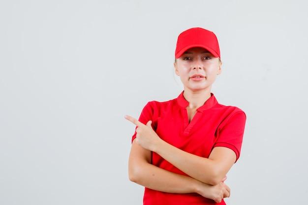 Livraison femme pointant vers le côté en t-shirt et casquette rouge et à la confiance