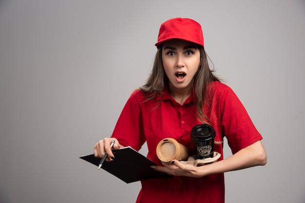 Livraison femme tenant des tasses à café et presse-papiers.