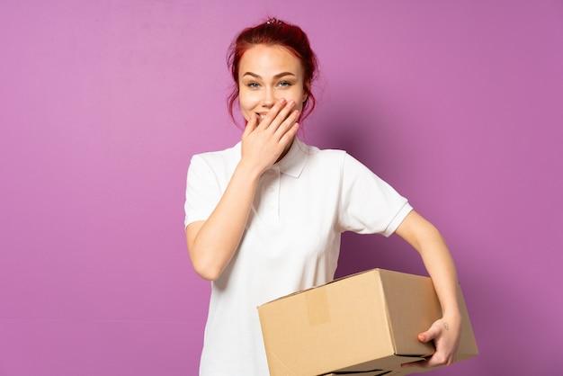 Livraison fille adolescente isolée sur fond violet heureux et souriant couvrant la bouche avec la main