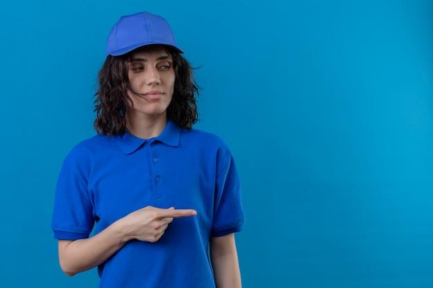 Livraison fille en uniforme bleu et cap à côté avec une expression suspecte pointant avec l'index sur le côté debout sur l'espace bleu