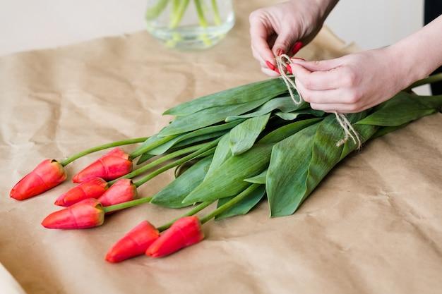 Livraison de fleurs. fleuriste organisant un bouquet de tulipes rouges. mains de femme nouent un arc de ficelle.