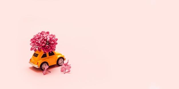 Livraison de fleurs fraîches pour les vacances. voiture jaune jouet avec branche de fleur lilas.