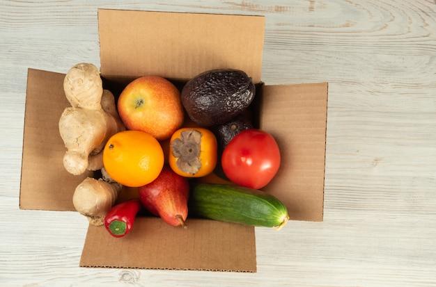 Livraison de fruits et légumes dans une boîte corton, la boîte est ouverte, sur une table en bois, vue de dessus.