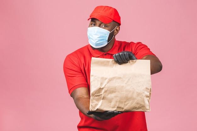 Livraison homme afro-américain employé en bonnet rouge t-shirt blanc uniforme masque facial gants tenir boîte en carton vide