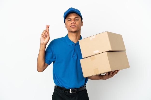 Livraison homme afro-américain isolé sur fond blanc avec les doigts croisés et souhaitant le meilleur