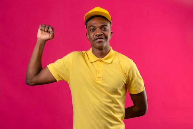 Livraison homme afro-américain en polo jaune et casquette à la confiance avec le sourire sur le visage levant le poing après un concept gagnant de la victoire sur rose isolé