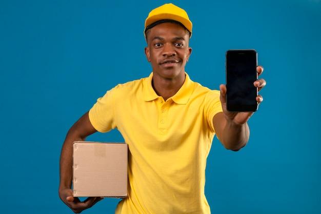 Livraison homme afro-américain en polo jaune et casquette holding box package montrant téléphone mobile avec sourire sur le visage debout sur bleu