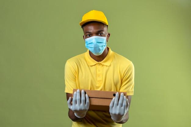 Livraison homme afro-américain en polo jaune et casquette portant un masque de protection médicale tenant des boîtes à pizza avec sourire sur le visage debout sur le vert