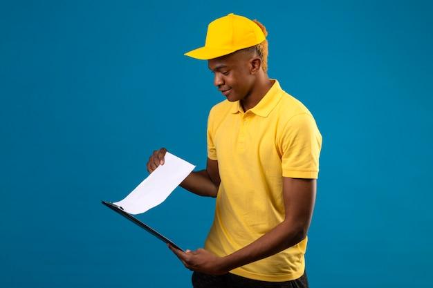 Livraison homme afro-américain en polo jaune et casquette à la recherche de blancs ta avec sourire sur le visage debout sur bleu isolé
