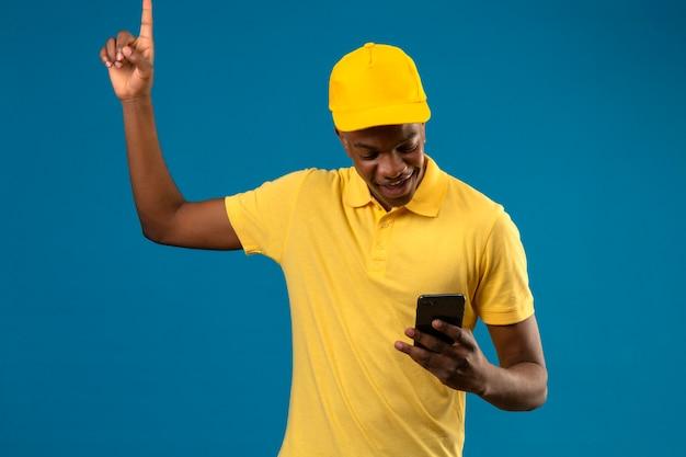 Livraison homme afro-américain en polo jaune et casquette regardant l'écran de son doigt pointig téléphone mobile up smiling standing on blue