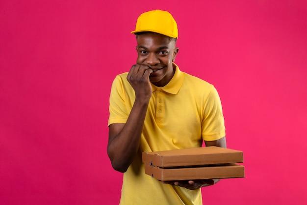 Livraison homme afro-américain en polo jaune et casquette à la sortie et anxieux mordre les ongles en attente de surprise souriant debout