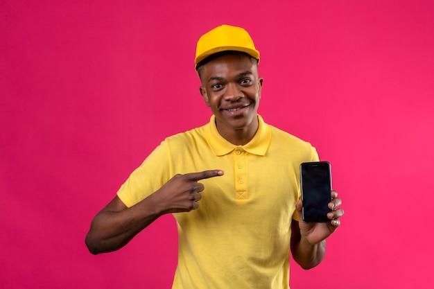 Livraison homme afro-américain en polo jaune et casquette souriant joyeusement pointant avec le doigt sur smartphone dans sa main sur rose